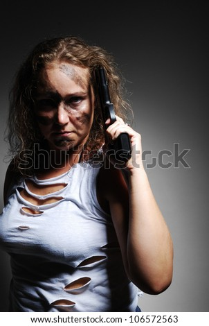 Severe woman is holding a gun near her temple and looking at the camera. Her face is disguised. She is wearing a rent T-shirt and torn jeans. - stock photo