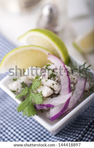 Seviche, decorated with lime, onion and coriander - stock photo