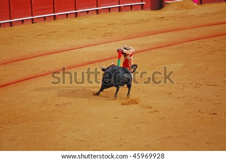 "SEVILLE - APRIL 30: Bullfighter David Fandila ""El Fandi"" sticks the banderillas into the bull at the Plaza de Toros de Sevilla April 30, 2009 in Seville, Spain. - stock photo"