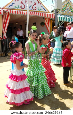 SEVILLE, SPAIN - APRIL 12, 2008 - Girls standing in front of a Casita in traditional dress at the Seville Fair, Seville, Seville Province, Andalusia, Spain, Western Europe, April 12, 2008. - stock photo