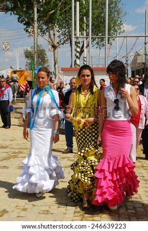 SEVILLE, SPAIN - APRIL 12, 2008 - Three women walking along the street in traditional dress at the Seville Fair, Seville, Seville Province, Andalusia, Spain, Western Europe, April 12, 2008. - stock photo