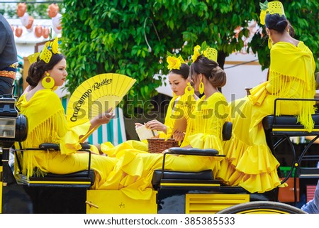 SEVILLE, SPAIN - APRIL 29, 2015: Young and beautiful women on a horse drawn carriage during the the April Fair of Seville on April, 29, 2015 in Seville, Spain - stock photo