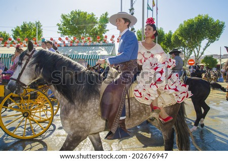 SEVILLE, SPAIN-MAY 8: People mounted on horse on fair of Seville on May 8, 2014 in Seville. - stock photo