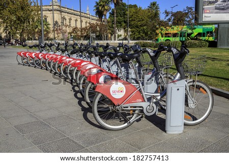 SEVILLE, SPAIN - NOVEMBER 27: A row of bicycles in the exchange program Sevici community in Seville Spain on November 27, 2013. People can rent bicycles for short trips, reducing traffic and pollution - stock photo
