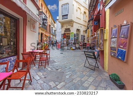 SEVILLE, SPAIN - OCTOBER 28, 2014: Little streets with the shops and restaurants in the Santa Cruz district - Calle Ximenez de Enciso street. - stock photo