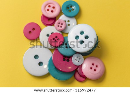 Sew buttons on a yellow background - stock photo