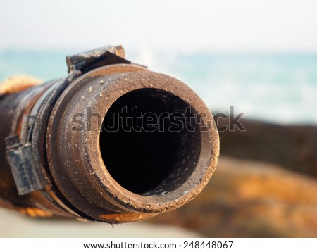 Sewage pipe is rusty and the background is the sea - stock photo