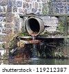 Sewage pipe on a dam - stock photo