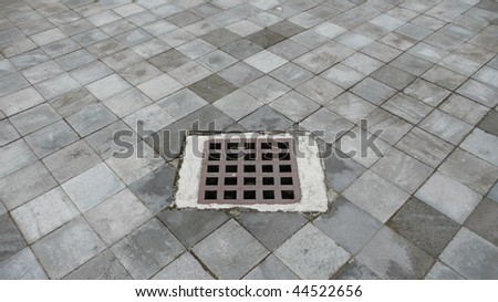 sewer cover at paved stone - stock photo