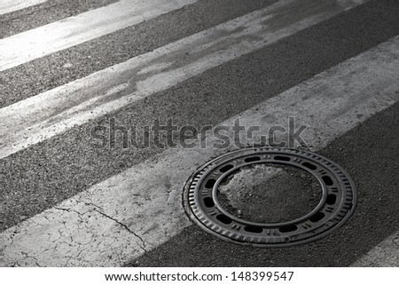 Sewer manhole cover on asphalt road with pedestrian crossing marking - stock photo