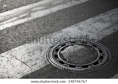 Sewer manhole cover on dark asphalt road with pedestrian crossing marking - stock photo