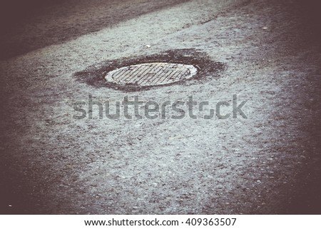 Sewer manhole cover on the new asphalt urban road. - stock photo