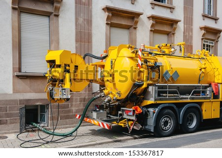 Sewerage truck on street working - clean up sewerage overflows, cleaning pipelines and potential pollution issues from an modern building. - stock photo