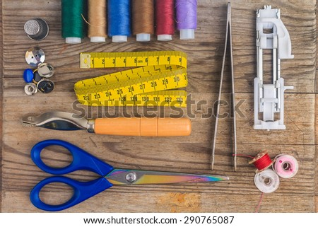 sewing accessories: colored threads, thimble, sewing tweezers, sewing foot, bobbins, scissors, measure tape, buttons - stock photo