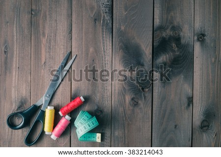 Sewing accessories on wooden table, top view - stock photo