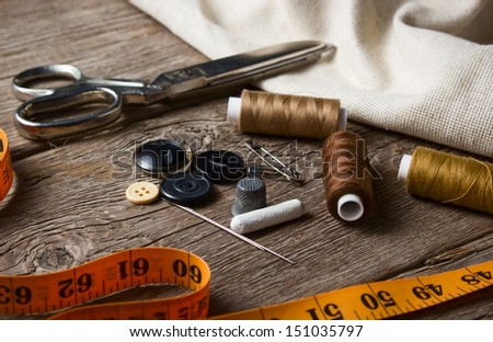 Sewing accessories: scissors, needle, thimble on wooden table - stock photo