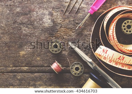 Sewing accessories.  scissors, needle, thimble on wooden table background, over light [vintage tone] - stock photo