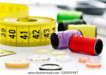 Sewing accessories: tape measure, buttons, spool and scissors - stock photo