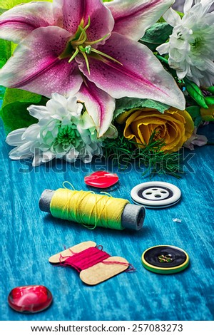 sewing accessories with bouquet of fresh flowers on turquoise background - stock photo