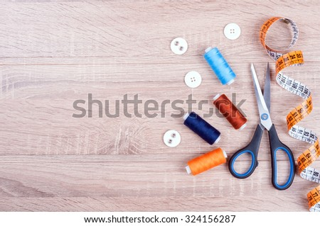 Sewing background. Accessories for needlework on wooden background. Spools of thread, scissors, buttons, measuring tape, sewing supplies. Set for needlework top view - stock photo
