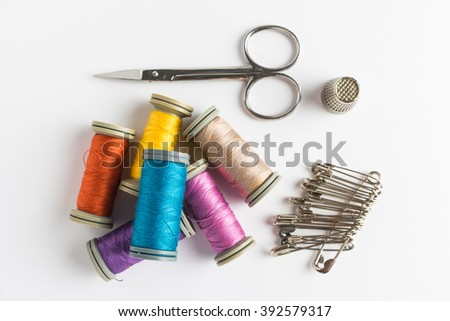 Sewing background. Accessories for needlework on wooden background. Spools of thread, scissors, sewing supplies. Set for needlework on white. Top view with copy space. - stock photo