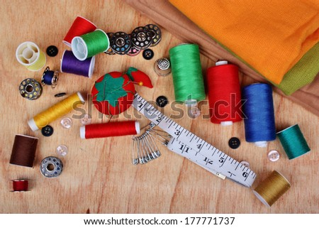 Sewing background items: buttons, colorful fabrics, material, measuring tape, bobbins, buttons, cloth, safety pins, needles, pincushion, thimble, spools of thread - stock photo