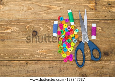 Sewing buttons, scissors and rolls of thread on a wooden background - stock photo