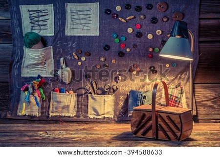 Sewing cloth made of buttons, needles and threads in tailor workshop - stock photo