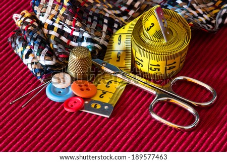 sewing kit accessories on red texture - stock photo