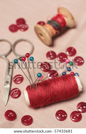 Sewing kit. Bobbins, scissors, buttons and pins. Focus is on the red bobbin with pins - stock photo