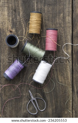 Sewing kit. Scissors and  bobbins with thread  on the rustic  background - stock photo