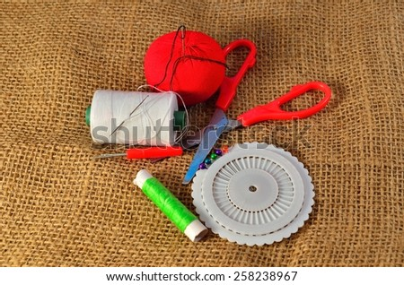 Sewing kit. Scissors, bobbins with thread and needles on the old fabric - stock photo