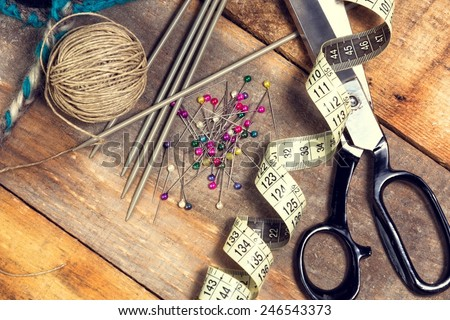 Sewing kit. Scissors, bobbins with thread, measure tape and needles on top of the old wooden table. - stock photo