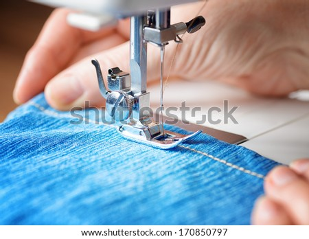 Sewing machine and blue jeans fabric. - stock photo