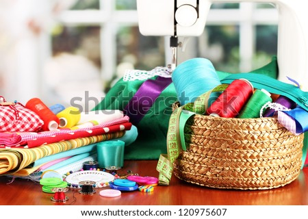 sewing machine and fabric on bright background - stock photo