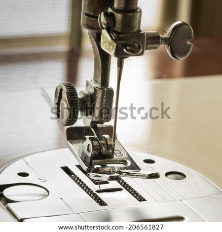 sewing machine and red thread - stock photo