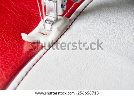 sewing machine and white and red leather with a seam close-up - stock photo