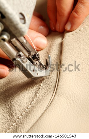 sewing machine in action for working leather for a sofa - stock photo