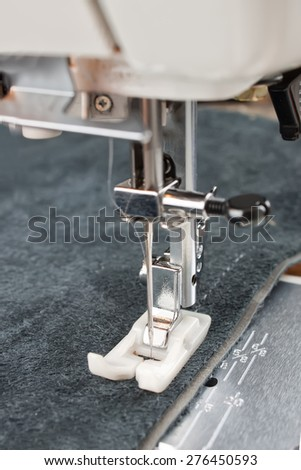sewing machine makes a seam on leather. sewing process - stock photo