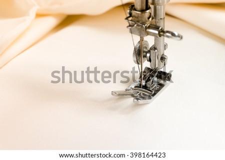 Sewing machine on fabric background - stock photo