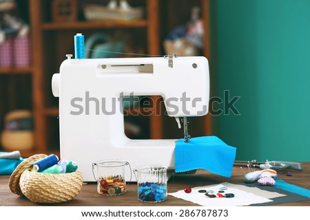 Sewing machine on table in workshop - stock photo