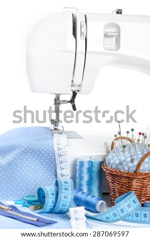 Sewing machine with cloth, thread, measuring tape and pincushion - stock photo