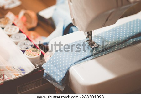 Sewing machine with many sewing utensils on a wooden table - stock photo