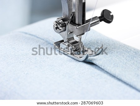 Sewing machine working part with blue cloth - stock photo
