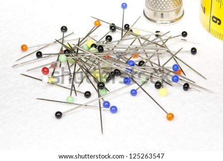 sewing: pins with thimble and tape - stock photo
