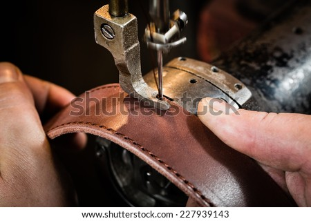 Sewing process of the leather belt. Man's hands behind sewing. Leather workshop. - stock photo
