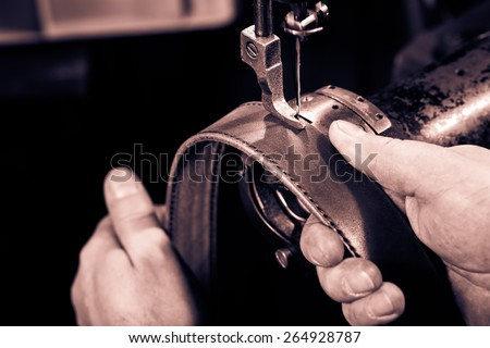 Sewing process of the leather belt. Man's hands behind sewing. Monochrome cream tone. Black and white photography. - stock photo