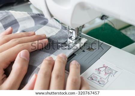 Sewing Process , the sewing machine sew women's hands sewing machine - stock photo