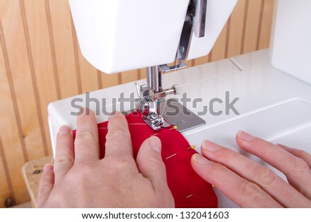 Sewing red fabric on sewing machine - stock photo