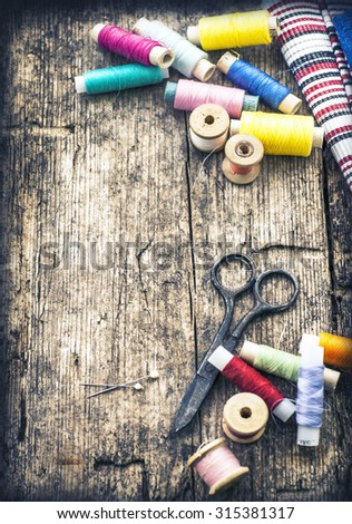 Sewing studio background with bobbins, needles, scissors and striped fabric on wooden table background - stock photo